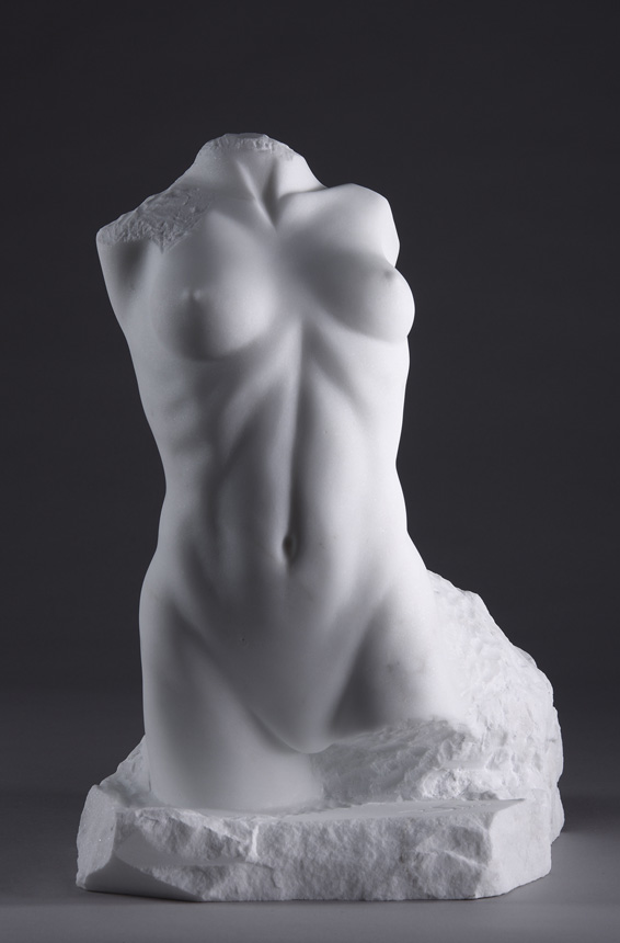 Entitled Lora, this is a photograph depicting a one-quarter life-size marble sculpture of a standing female figure emerging from the stone base, created by sculptor Blake Ward