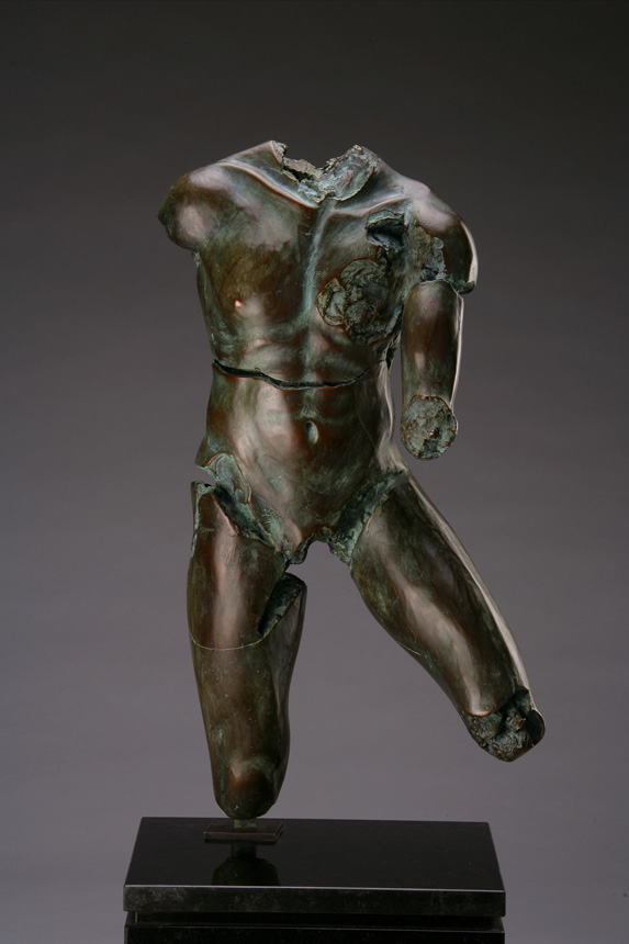 Entitled Gator BLU-92, this is a photo of a fragment of a one-quarter life size bronze sculpture. Depicted is the torso of a nude male figure missing his legs from the knees down his right arm and head and neck. By sculptor Blake Ward.