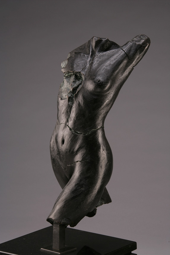 Entitled Putkimiina M-68, this is a photo of a fragment of a one-quarter life size bronze sculpture. Depicted is the torso of a nude female figure missing her legs from above the knees, both arms and head. By sculptor Blake Ward.
