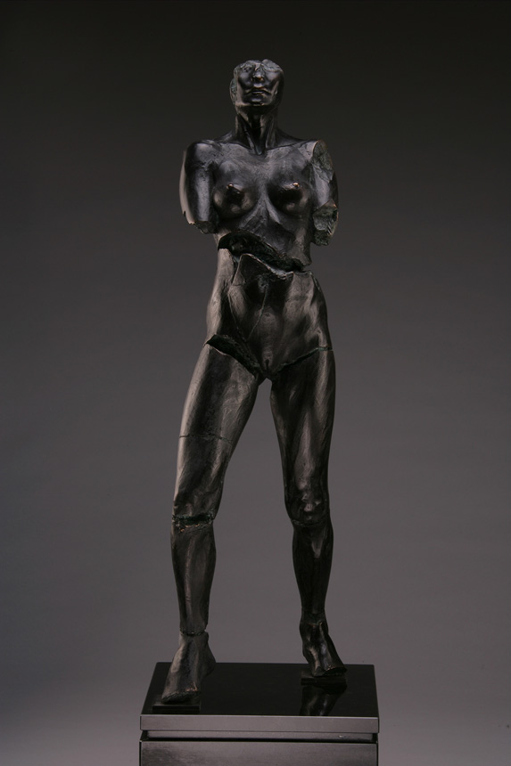 Entitled Rockeye CBU-87, this is a photo of a fragment of a one-quarter life size bronze sculpture. Depicted is standing nude female figure missing part of her feet, both arms above the elbow and her head above the nose. By sculptor Blake Ward.