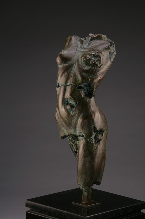 Entitled Vlamara 69, this is a photo of a fragment of a one-quarter life size bronze sculpture. Depicted is the torso of a nude female figure missing her legs from the knee down and both her arms and head. By sculptor Blake Ward.