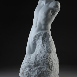 Entitled Layton, this is a photograph depicting a one-quarter life-size marble sculpture of a standing male figure emerging from the stone base, created by sculptor Blake Ward