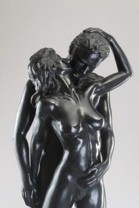 Entitled Les Amoureux or The Lovers, this is a photograph depicting a two, one-quarter life-size bronze sculptures of a standing male holding a female figure, created by sculptor Blake Ward