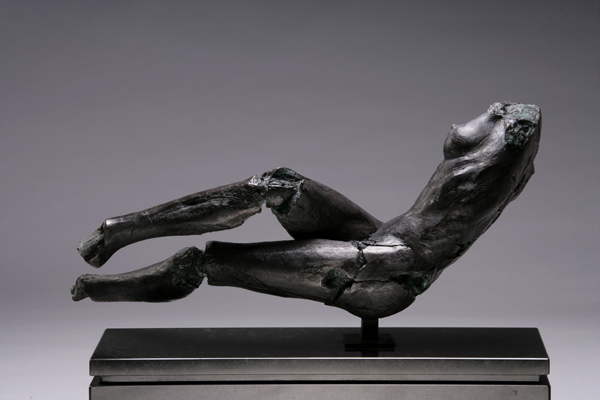 Entitled Hamdy HAK-1, this is a photo of a fragment of a one-quarter life size bronze sculpture. Depicted is a lying nude female figure missing her feet, arms, neck and head. By sculptor Blake Ward.