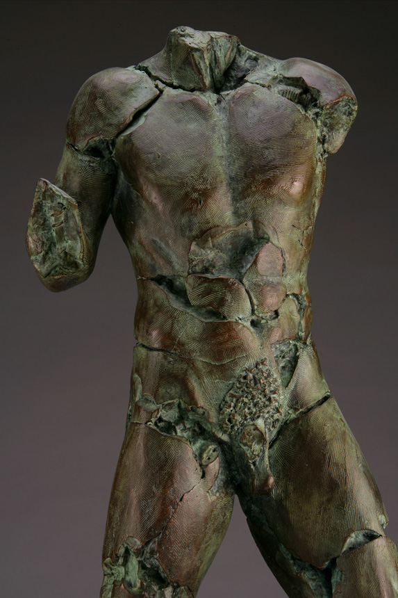 Entitled Scatmine BLU-92, this is a photo of a fragment of a one-quarter life size bronze sculpture. Depicted is standing nude male figure missing his legs at above the knee, both arms and head. By sculptor Blake Ward.