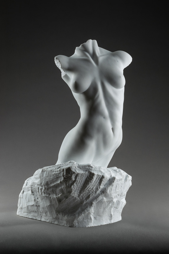 Entitled Adrianna, this is a photograph depicting a one-quarter life-size marble sculpture of a standing female figure emerging from the stone base, created by sculptor Blake Ward