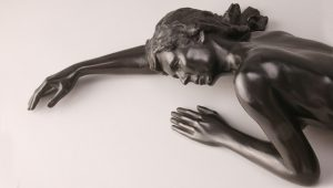 Entitled Lau, this is a photograph depicting a one-quarter life-size marble sculpture of a laying female figure, created by sculptor Blake Ward