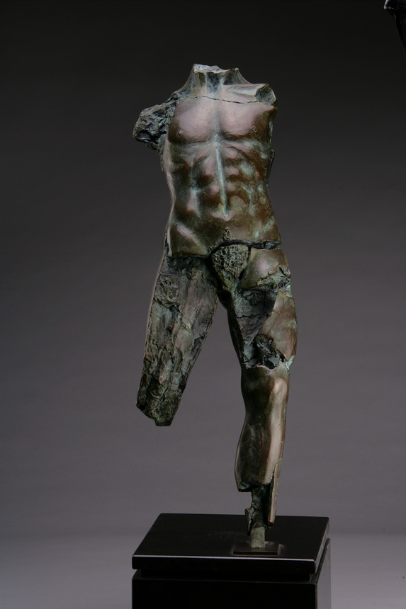Entitled POMZ 2M, this is a photo of a fragment of a one-quarter life size bronze sculpture. Depicted is standing nude male figure missing his legs above the knee, both arms and head. By sculptor Blake Ward.