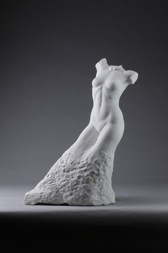 Entitled Sharon, this is a photograph depicting a one-quarter life-size marble sculpture of a standing female figure emerging from the stone base, created by sculptor Blake Ward