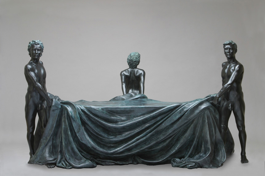 Entitled The Bench, this is a photograph depicting three one-quarter life-size bronze standing figures; two male and one female. They are holding a cloth draped over a bench, the male figures holding each end of the bench and the female stands at the back in the middle. Created by sculptor Blake Ward
