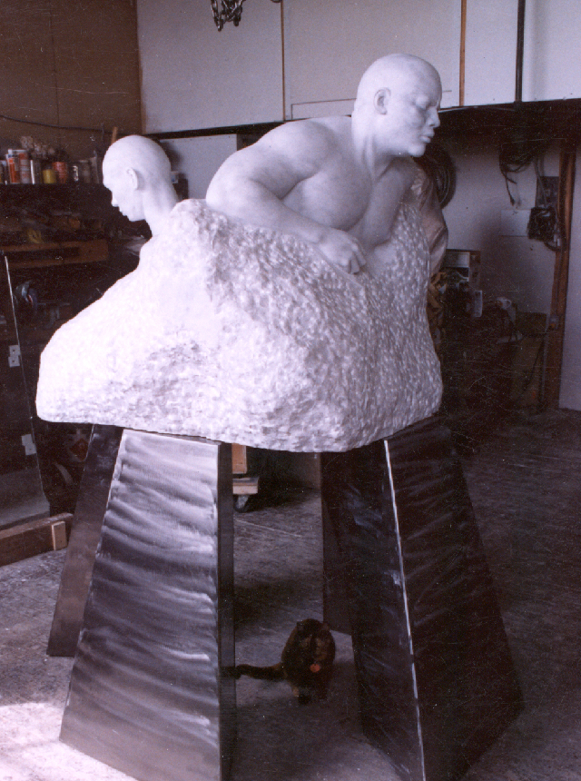 This photo shows a large block of roughly hewn white marble in a pyramid like shape. Emerging from the block of stone are two men back to back facing away from each other. On the left is shown the head, neck and top of the shoulders of a bald Chinese male coming out of the block. This portrait shows the side of the young man's face and the top of his shoulders. His head is bowed his mouth closed and his eyes are cast downward. On the right carved from the marble is the upper body with right arm and head of a large male figure looking straightforward. This figure is leaning forward as if moving in that direction, his massive arm is bent at the elbow and ends in a clenched fist. This male is bald and has the facial features of a person of African origin with a wide nose and generous lips.