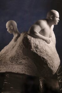 Entitled 1989: Emerging Continents this is a photograph of a large marble sculpture of two male figures, back to back, emerging from the stone base, created by sculptor Blake Ward