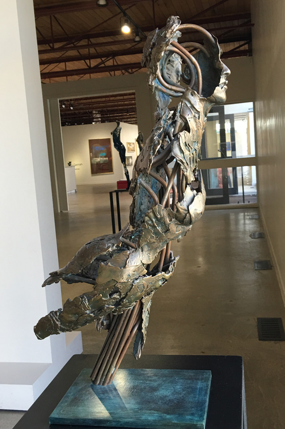 Photo of a one-quarter life-size partial female figure in bronze with an exposed interior structure by Blake Ward Blake Sculpture